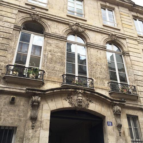 L'hôtel Le Rebours - La façade sur la rue et le portail orné d'un mascaron représentant un satyre