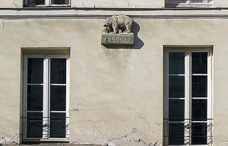 La cour de l'Ours : bas-relief représentant un ours sur la façade du bâtiment sur rue